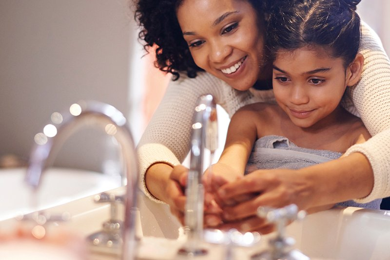 Mom and Daughter washing hands together at the bathroom sink
